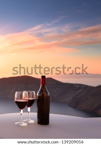 Wine bottle and glasses overlooking Santorini cliffs - stock photo