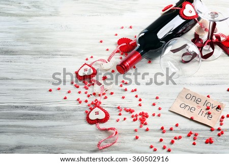 Wine bottle and glasses with handmade hearts on white wooden background - Valentine's concept - stock photo