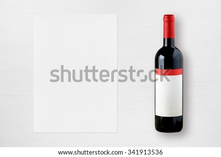 Wine bottle and paper for wine list on white table - stock photo