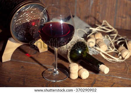 Wine bottle and small barrel with glass on old wooden background. Vintage colors. - stock photo