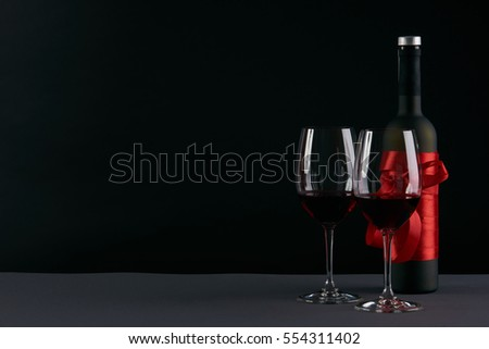 Wine bottle and two wineglasses on a dark background. Love card concept with copy space, Valentine's day theme