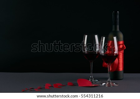 Wine bottle and two wineglasses with red hearts on a dark background. Love card concept with copy space, Valentine's day theme