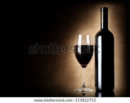 Wine bottle and wineglass on a old background - stock photo