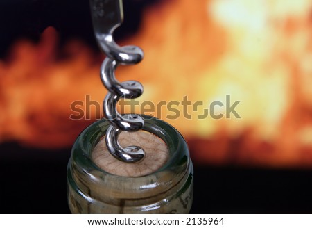 Wine bottle by orange flames with silver corkscrew, macro, close up - stock photo