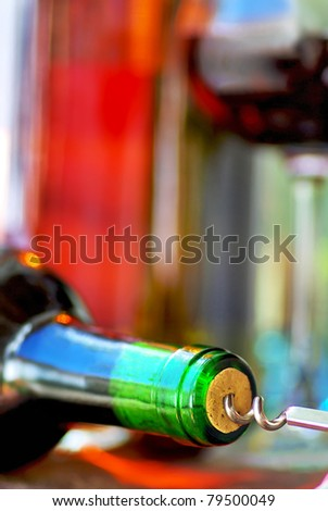 Wine Bottle closeup and corkscrew. - stock photo