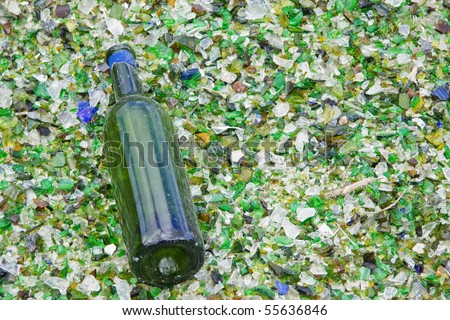 Wine bottle lying on a bed of broken glass having escaped the crusher at a  recycling facility in UK - stock photo