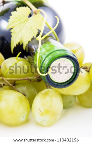 Wine bottle of grape leaves and grapes. - stock photo