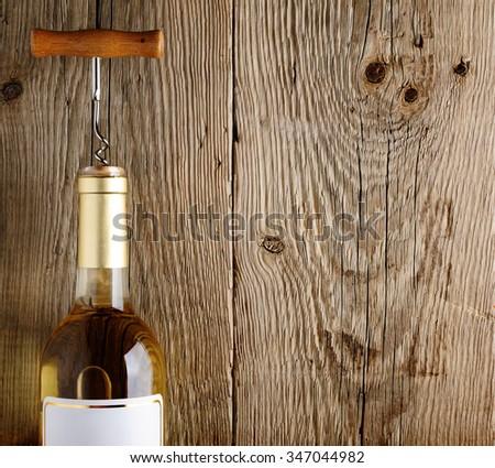 Wine bottle on old wooden background - stock photo
