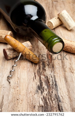 Wine bottle with corkscrew and cork - stock photo