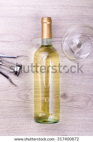Wine bottle with corkscrew on wooden background. - stock photo