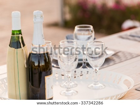 Wine bottles and glasses set on table - stock photo