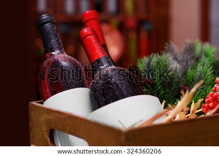 Wine bottles in decorated box on unfocused background - stock photo