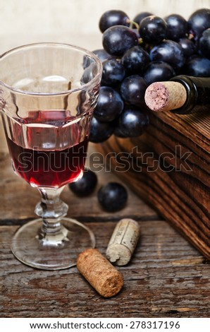 Wine bottles in wooden boxes, crystal glass with red wine and grapes are on the wooden background.Soft focus. - stock photo