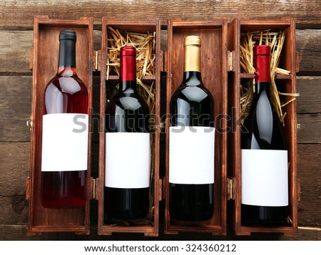 Wine bottles in wooden cases, close up. - stock photo