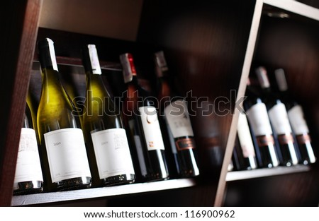 Wine bottles on a wooden shelf. - stock photo