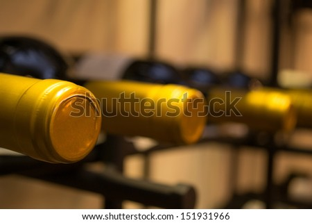 Wine bottles stacked on racks shot with limited depth of field - stock photo