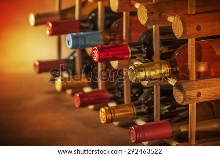 Wine bottles stacked on wooden racks shot with very limited depth of field - stock photo