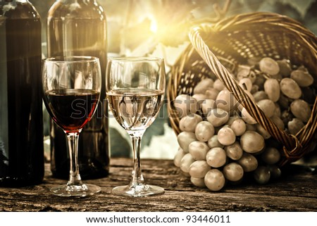 Wine bottles, two glasses and bunch of grapes in basket against vineyard in spring. Vintage look - stock photo