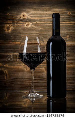 Wine bottles with glass on wooden background