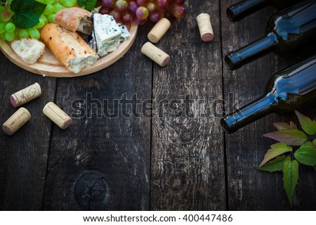 Wine bottles with grape leaves on wooden background with copy space, selective focus - stock photo