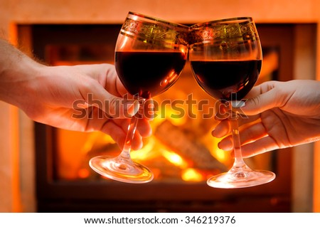 Wine by the fireplace, glasses of wine. - stock photo