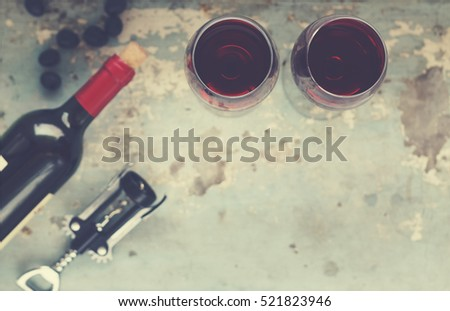Wine by the glass, grapes, bottle of wine, a corkscrew on vintage blue background. Thanksgiving. Top view, closeup, selective focus