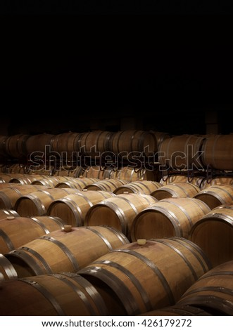 Wine cellar in warm ambiance.  Wooden wine barrels at a winery. Black background