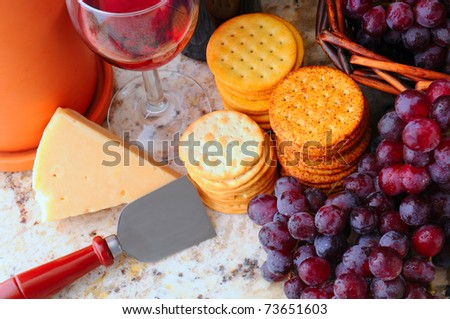 Wine, cheese, crackers and grapes still life. Horizontal format viewed from a high angle. - stock photo