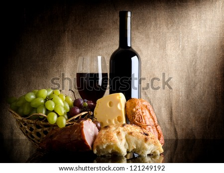 Wine, cheese, grapes and sausage on an old canvas - stock photo