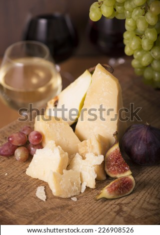 wine, cheese, grapes, figs on a wooden background
