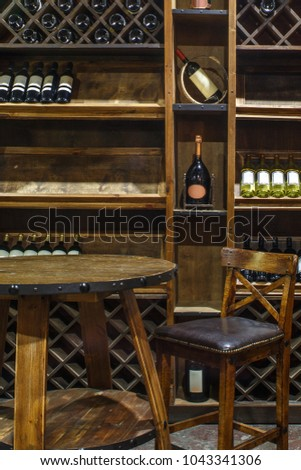 wine chiller cabinet in wine cellar in restaurant, wine room interior, hardwood furniture, oak table and oak bar stool