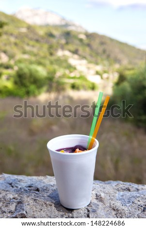 Wine cocktail with fruits (sangria) in plastic cup on nature background - stock photo