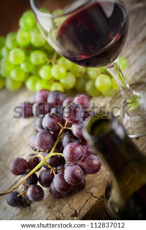 Wine concept. Food and drink background with red wine, fresh grapes and wine bottle - stock photo
