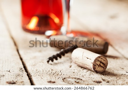 Wine cork and corkscrew on wooden table, wine bottle and glass on the background