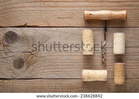 Wine corks and corkscrew on wooden background - stock photo
