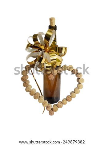 wine corks in the form of heart and a bottle of wine with golden bow, white background - stock photo
