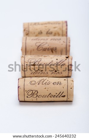 "Wine Corks lined up on white. You can read ""Mis en Bouteille a la (dans nos) caves"" on them which means ""Bottled in our caves"". Selective focus is going from the front to the back. - stock photo"