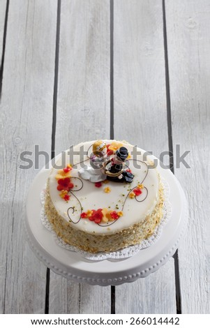 Wine cream cake, wedding cake with figurines, bride and groom - stock photo