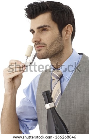 Wine-expert smelling cork after opening bottle of wine.