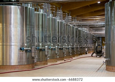 Wine Fermenting in huge vats in a famous wine cellar in spain. Ground level. - stock photo