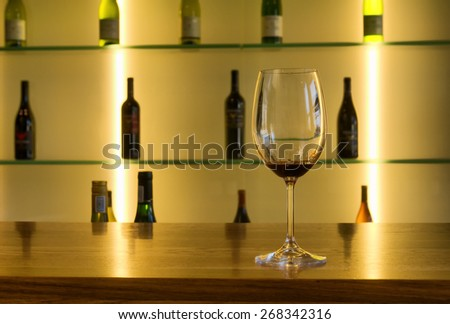 Wine glass against array of bottles - golden light, focus on glass. Shot in Western Cape, South Africa.