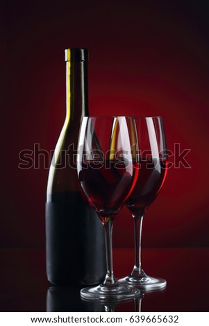 Wine glass and bottle with red wine on red background