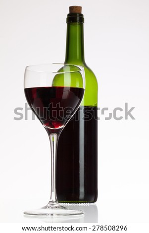 Wine glass and bottle with red wine on white table - stock photo