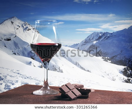 Wine glass and chocolate with winter mountainscape - stock photo