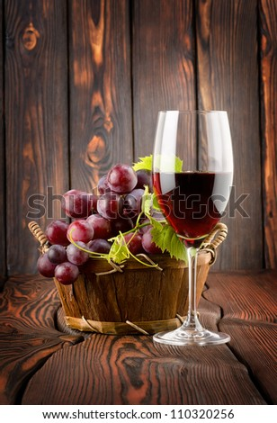 Wine glass and grapes in a basket - stock photo