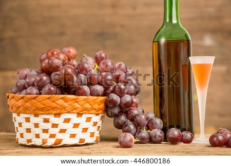 Wine glass and red grape with wooden background