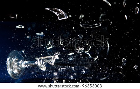 Wine glass breaking into pieces on a blue surface - stock photo