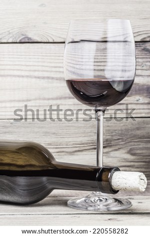 Wine glass, cork and bottle on a wooden background