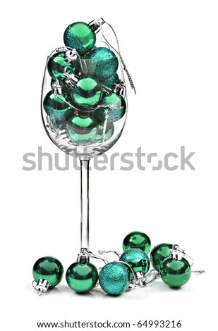 Wine glass filled with turquoise christmas decorations - stock photo