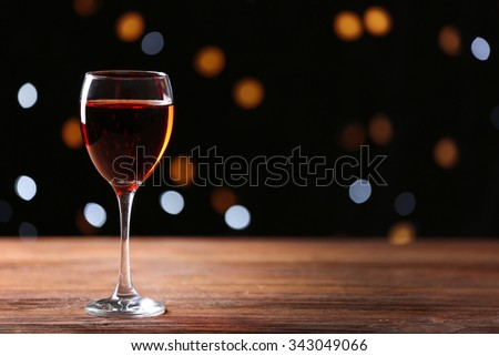 Wine glass on wooden table against defocused lights background - stock photo